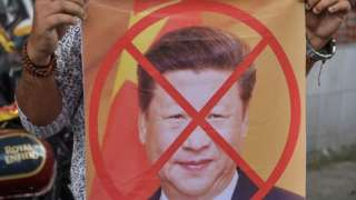 Protestor in Delhi holding picture of Xi Jinping