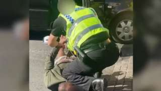 Still from a video showing a policeman appearing to kneel on a black man's neck during an arrest