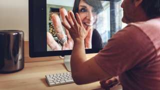 Man and woman hold hands via video conference