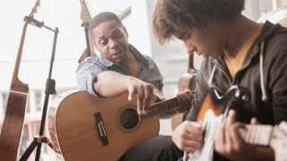 Um homem ensinando um adolescente a tocar violão/guitarra