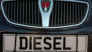 A diesel sign is displayed on the front of a second hand car for sale parked on a used car lot