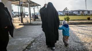 A woman walks with her child at a camp in northeastern Syria