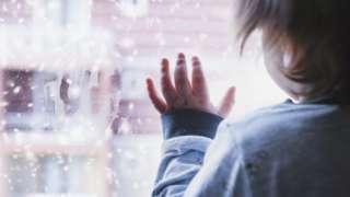 Menino olhando pela janela em um dia de neve
