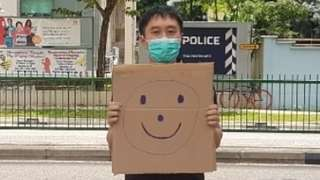 Jolovan Wham holds up a smiley face sign outside a police station
