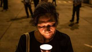 Woman with candle in Hong Kong on Wednesday