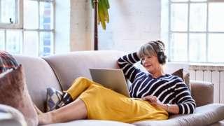 woman wearing headphones watching movie on laptop