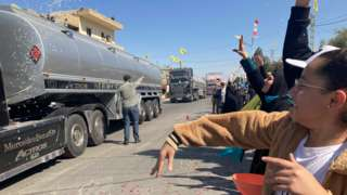Women throw flower petals at lorries brining Iranian fuel from Syria into Lebanon, in the village of al-Ain (16 September 2021)