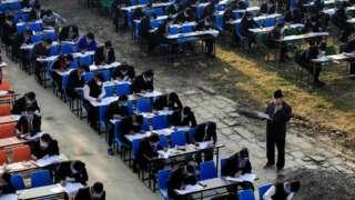 नेपालको राजधानी काठमाण्डूमा दूरी काम गर्दै मास्क लगाएर कक्षा १२ को परीक्षा दिइरहेका विद्यार्थीहरू।
