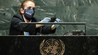A United Nations employee cleans the microphones at the podium after Brazil's President Jair Bolsonaro spoke and before the start of U.S. President Joe Biden's address the 76th Session of the U.N. General Assembly on September 21, 2021 at U.N. headquarters in New York City