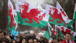 People waving Welsh flags on St David's Day