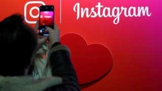 Девојка снима лого Инстаграма мобилним телефоном