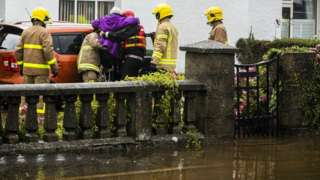 lady being rescued from floodwater