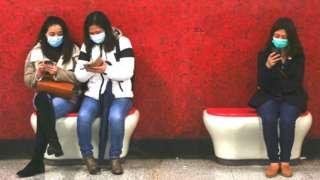 People wearing masks looking at phones