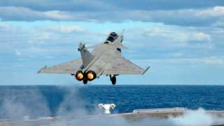 French fighter jet taking off from aircraft carrier.