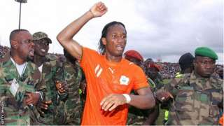 Drogba is escorted from the Bouake pitch by security personnel