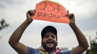 """A man holds a placard reading """"23F Our Day"""""""