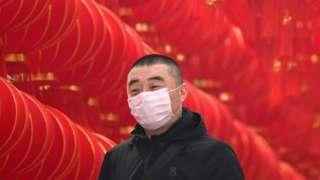 Un hombre en China usando una mascarilla.