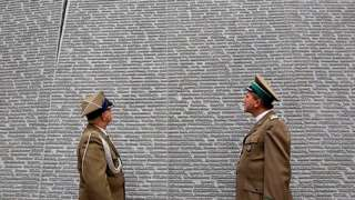 Polish soldiers stand in front of a wall with names engarved at Bykivnia