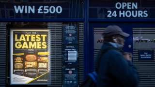 A man walks past a casino advertising fixed odds betting terminals