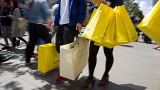 Shoppers carry bags from a Selfridges store