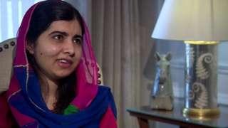 Com véu, Malala sorri enquanto fala em entrevista