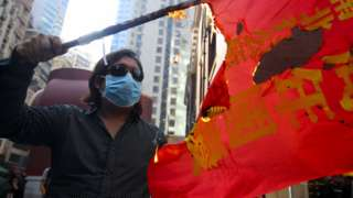 An anti-government protesters burns a commemorative banner in protest of National Day in Hong Kong, China, 01 October 2019