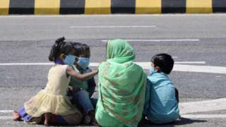 migrant worker with children headed back home pauses for break, on day 5 of the nationwide lockdown imposed by PM Narendra Modi to check the spread of coronavirus, at Yamuna expressway zero point, on March 29, 2020 in Noida, India. (Photo by Sunil Ghosh /Hindustan Times via Getty Images)
