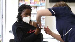 A woman receives her first dose of the Pfizer vaccine on June 6, 2021 in Stanmore, Greater London.