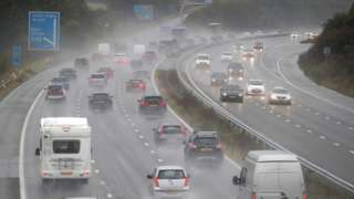 Cars make their way along the M4 motorway near to junction 18, as heavy rain lashes the UK