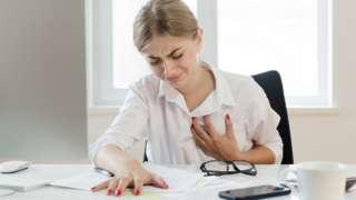 Una mujer en un escritorio se siente el pecho