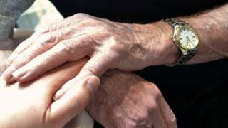 A generic photo of elderly hands holding younger hands