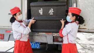 Employees carry a box of wheat cakes stuffed with meat, produced by the Kumsong Foodstuff Factory, to a movable vendor stall in the Central district in Pyongyang