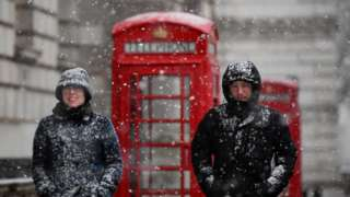 People walk in the snow in central London