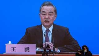 Chinese Foreign Minister Wang Yi is seen on a screen as he speaks to reporters during an online press conference, in Beijing