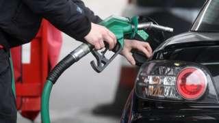 Motorist using a petrol pump