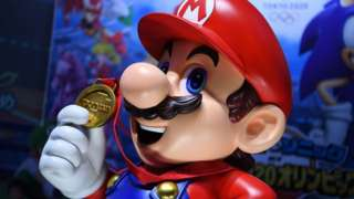A real-world Mario statue holds a gold medal in this photo