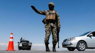 An Afghan National Army soldier stands guard at a checkpoint near Kabul in April 2021