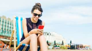 Woman sitting in a deckchair looking at her phone