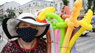 A woman in a face mask selling balloon swords smiles at the camera in Tbilisi, Georgia