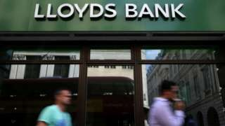 People walk past Lloyds bank branch