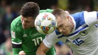 Northern Ireland striker Kyle Lafferty competes against Toni Sunjic of Bosnia-Herzegovina