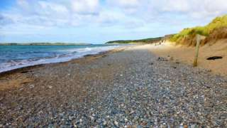 A dad and two children were rescued from Llanddwyn beach, Anglesey