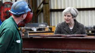 Theresa May with a worker at a steel works in Newport