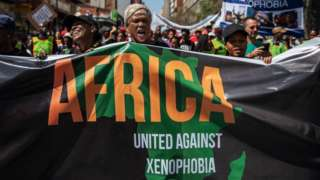 Woman with anti-xenophobia banner