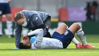 Trezeguet lies on the pitch as a physio attends to him