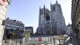 A man stares up at the charred front of the cathedral in Nantes