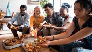 housemates sharing a pizza
