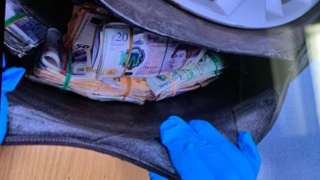 Spare tyre opened to reveal bags of cash