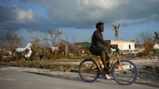 A woman rides a bicycle past damage in a destroyed neighborhood in the wake of Hurricane Dorian in Marsh Harbour
