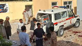 Afghan men stand next to an ambulance after a bomb attack at a mosque in Kunduz, Afghanistan, 8 October 2021